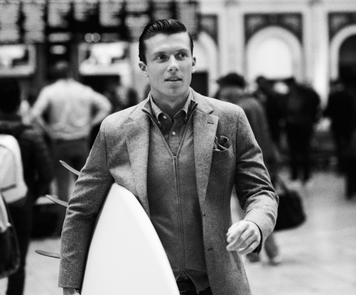 Man with suit holding a surf board