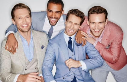 4 men laughing on their suits