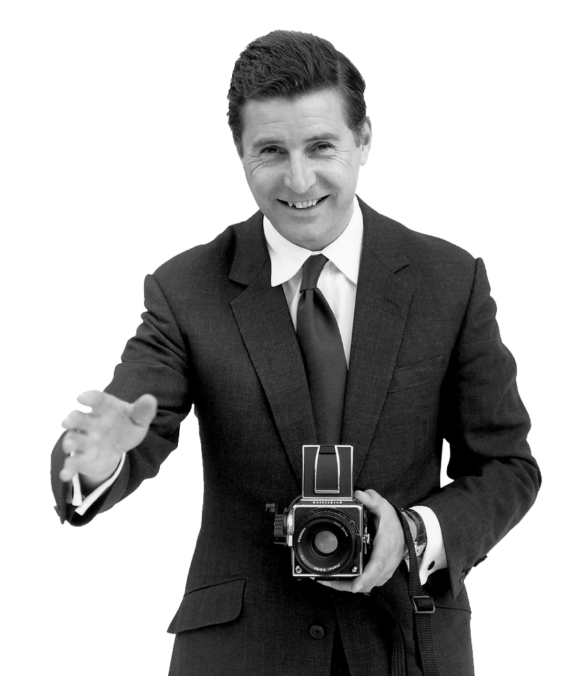 Jeremy Hacket, founder of Hackett, waving his hand and holding an old camera
